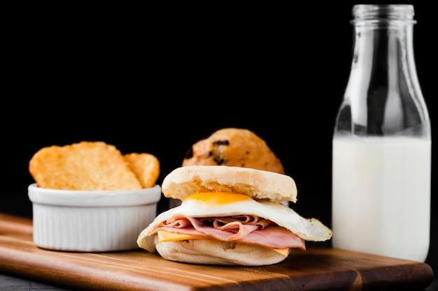 Close-up set benedict egg sandwich next to milk bottle Free Photo