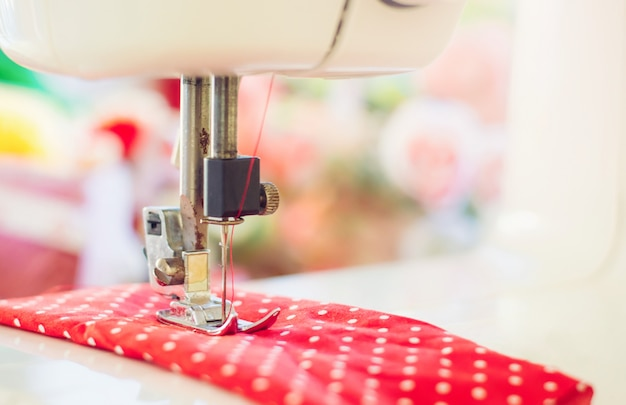 Close up of sewing machine working with red fabric Premium Photo