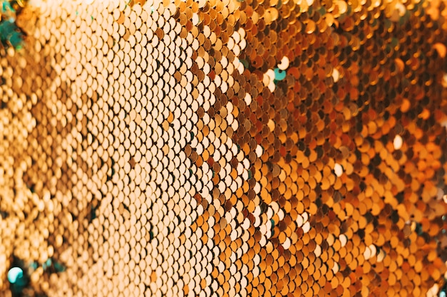 Close-up of shiny golden sequin material Free Photo