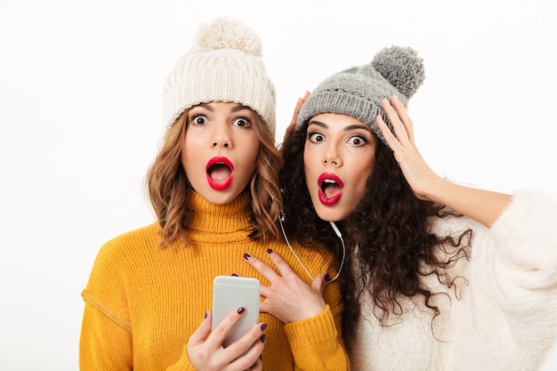 Close up shocked girls in sweaters and hats standing together with smartphone  over white wall Free Photo