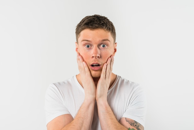 Close-up of shocked young man with his hand on cheeks against white background Free Photo
