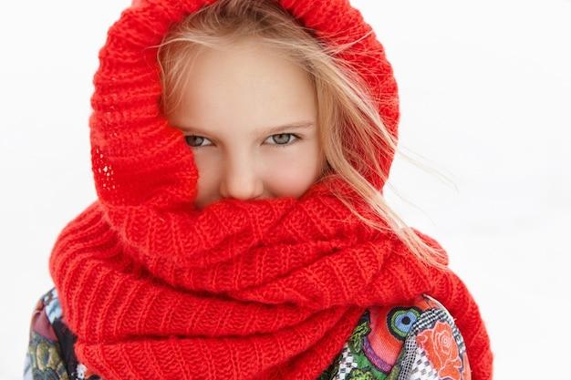 Immagine ravvicinata di adorabile bambina che sente freddo mentre cammina all'aperto Foto Gratuite