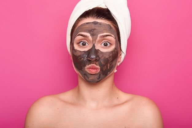 Primo colpo di bella femmina, ha la maschera di cioccolato sul viso, tiene gli occhi ben aperti e le labbra arrotondate, si pone con il corpo nudo, ha un asciugamano bianco sulla testa, avendo riposo nel salone spa, isolato sul muro rosa. Foto Gratuite