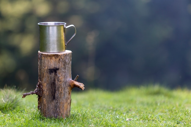 Close-up shot, big shiny tin mug on isolated tree stump outdoors on grassy sunny summer forest Premium Photo