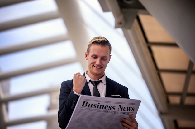 Close-up shot of a businessman in black suite reading the latest news Premium Photo