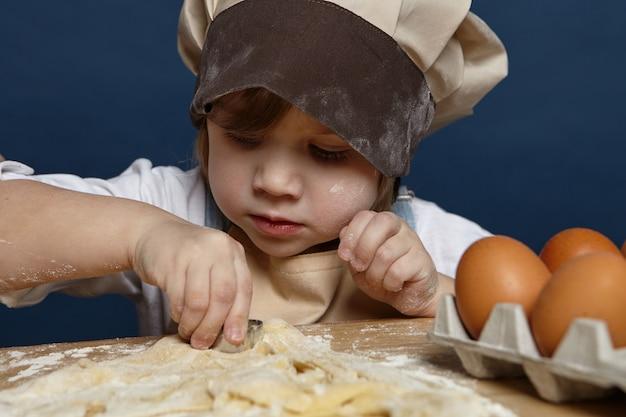 Immagine ravvicinata di affascinante ragazza carina che indossa un grande cappello da chef facendo i biscotti al tavolo della cucina, utilizzando stampi da forno, avendo concentrato l'espressione concentrata bambini, cucina e concetto di cottura Foto Gratuite