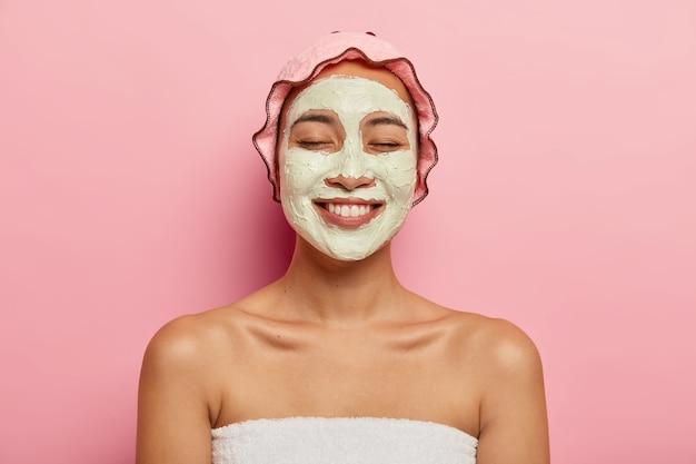 Immagine ravvicinata di felice femmina giapponese applica una maschera cosmetica, vuole avere una pelle fresca, ricrea nella località termale, mostra le spalle nude, indossa la cuffia da bagno, ha un ampio sorriso, isolato sul muro rosa Foto Gratuite