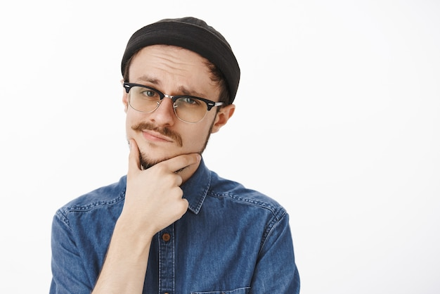 Close-up shot of doubtful smart suspicious handsome young guy with beard and moustache in black beanie and glasses touching chin and smirking squinting feeling uncertain and unimpressed Free Photo