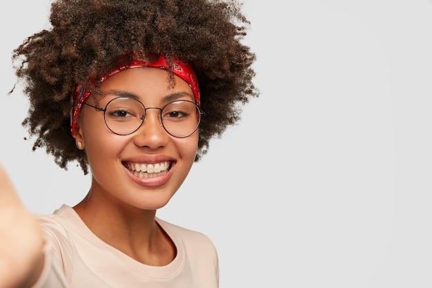 클로즈업 샷 기쁜 여성 소녀는 이빨 미소, 아프로 헤어 스타일, 아름다운 깨끗한 피부, 투명 안경 착용, 인식 할 수없는 장치를 들고 손을 뻗고 흰 벽 위에 셀카 만들기 무료 사진