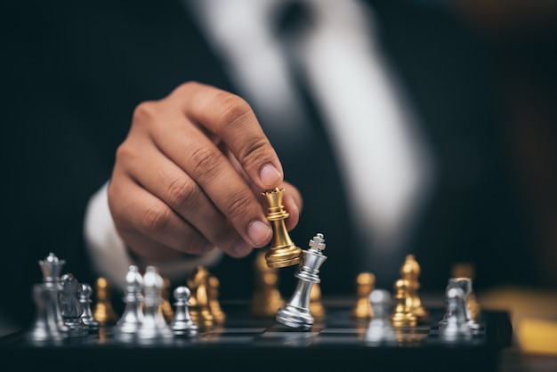 Close up shot golden chess to defeat killing silver king chess on white and black chess board for business challenge competition winner and loser concept Premium Photo