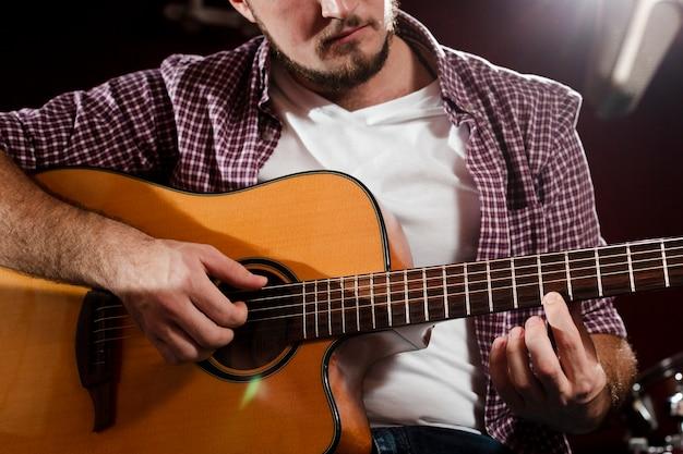 Close-up shot of guy playing guitar Free Photo
