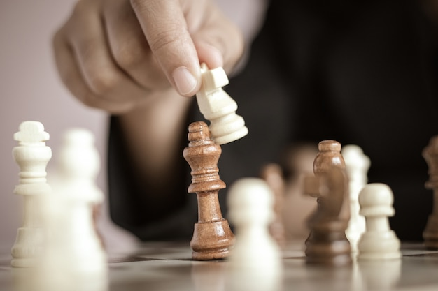 Close up shot hand of business woman playing the chess board select focus shallow depth of field Premium Photo