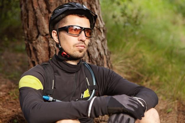 Immagine ravvicinata di bel ciclista con la barba rilassante dopo l'allenamento Foto Gratuite