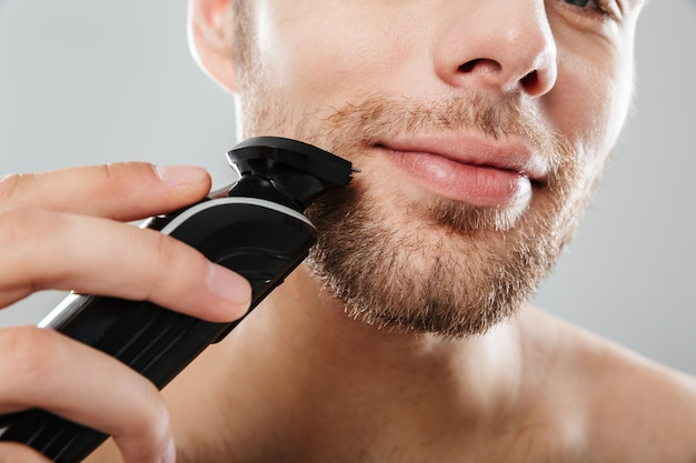 Close up shot of handsome man smiling while shaving his face with electric shaver making morning procedure in bathroom against grey wall Free Photo
