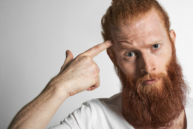 Immagine ravvicinata di un bel giovane uomo dai capelli rossi europeo con le lentiggini e la barba sfocata che si acciglia, fissando la telecamera con rabbia o indignazione come se dicesse: sei pazzo. espressioni facciali umane Foto Gratuite