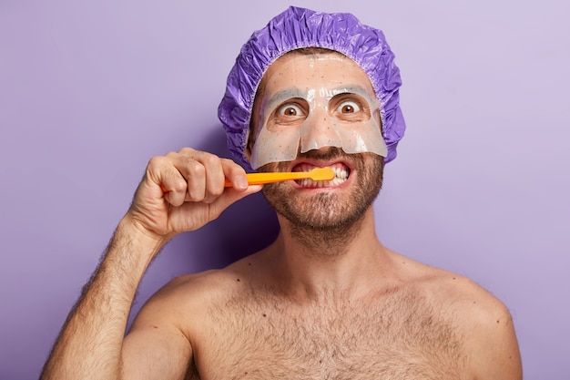 Immagine ravvicinata di uomo felice lava i denti al mattino, applica la maschera di bellezza, indossa la cuffia per la doccia Foto Gratuite