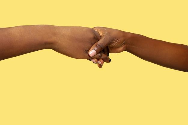 Immagine ravvicinata di mani umane che tengono isolato sulla parete gialla. concetto di relazioni umane, amicizia, collaborazione, famiglia. copyspace. Foto Gratuite
