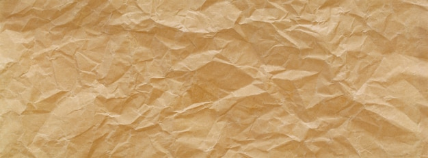 Close up shot of light brown crumpled recycled paper texture banner background Premium Photo