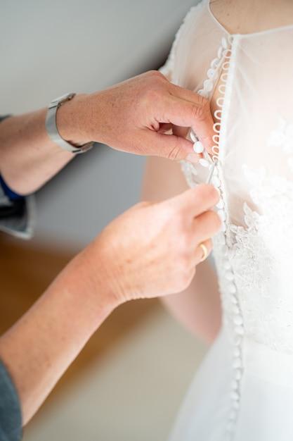 아름다운 웨딩 드레스 지퍼를 돕는 사람의 총을 닫습니다 무료 사진