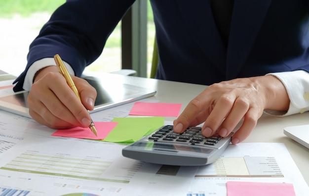 Аналитики с близкого расстояния используют калькулятор и ручку, чтобы оценить колеблющуюся ситуацию на фондовом рынке. Premium Фотографии