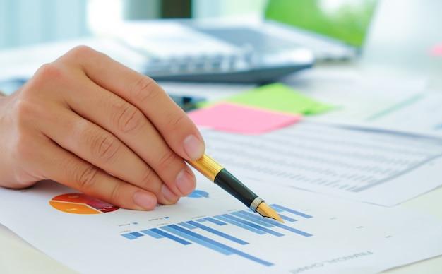 Съемка крупным планом аналитики используют ручку, чтобы указать на график, чтобы оценить ситуацию на фондовом рынке, который колеблется. Premium Фотографии