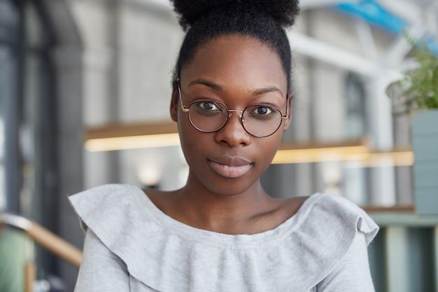 黒い肌の魅力的な深刻な女性のショットをクローズアップ、自信を持って直接カメラを見て、丸い眼鏡をかけて、オフィスでポーズをとって、仕事の後休憩しています。 無料写真