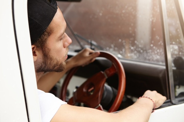 ホイールに手で彼の白いサファリ車内に座っているtシャツと野球帽を後ろに着て魅力的な若い白人ヒップスターのショットを閉じる 無料写真