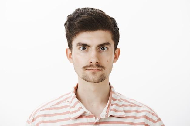 Снимок крупным планом спокойного и уверенного мужчины-модели в полосатой рубашке, небрежно стоящего и уверенного в себе, когда он добровольно сдает кровь Бесплатные Фотографии