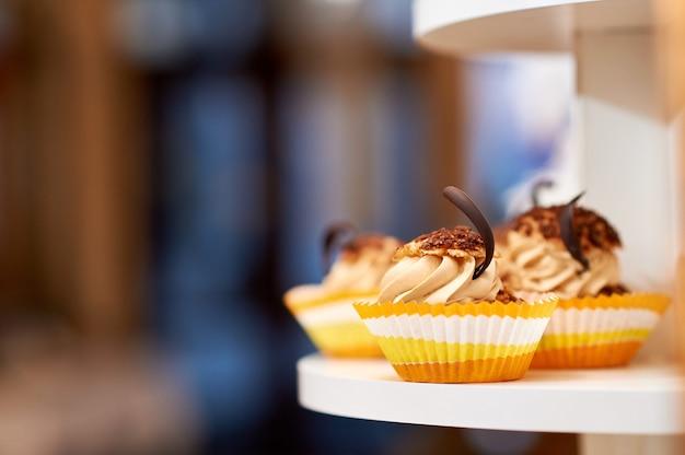 砂糖の甘い概念を食べるクリームとチョコレートの装飾copyspace食品とキャラメルバニラカップケーキのショットを閉じます。 無料写真