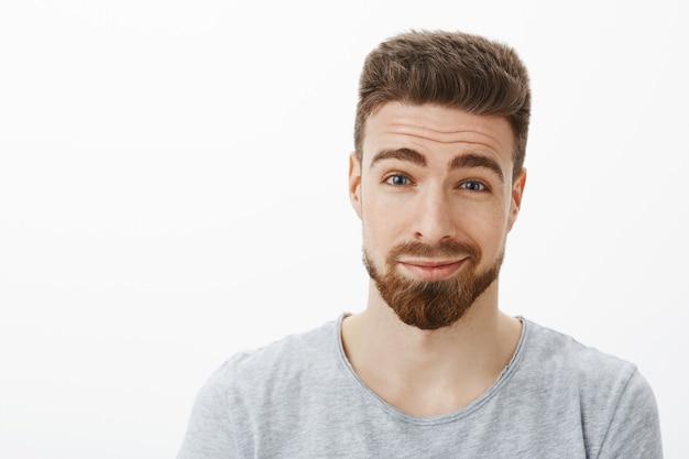 Снимок крупным планом обаятельного, доброго и харизматичного счастливого бородатого мужчины с усами, поднимающими брови и ухмыляющимся от восторга и нежных чувств, разглядывающих любовью и радостью Бесплатные Фотографии