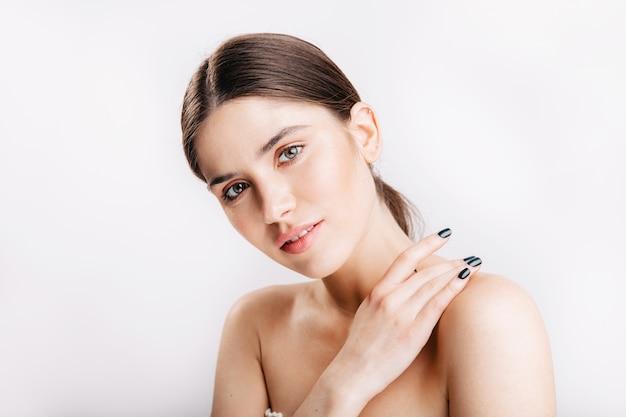 Снимок крупным планом очаровательной молодой девушки с идеально чистой кожей, нежно улыбаясь на белой стене. Бесплатные Фотографии