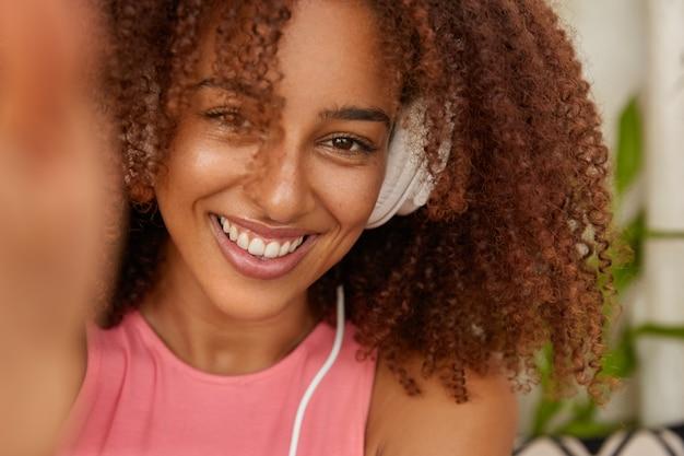 陽気な女性のクローズアップショットは、くっきりとした髪、歯を見せる笑顔、レクリエーションの時間を楽しんで、面白がって、ヘッドフォンで好きな音楽を聴き、自分撮りの肖像画を作り、屋内でモデルを作ります 無料写真