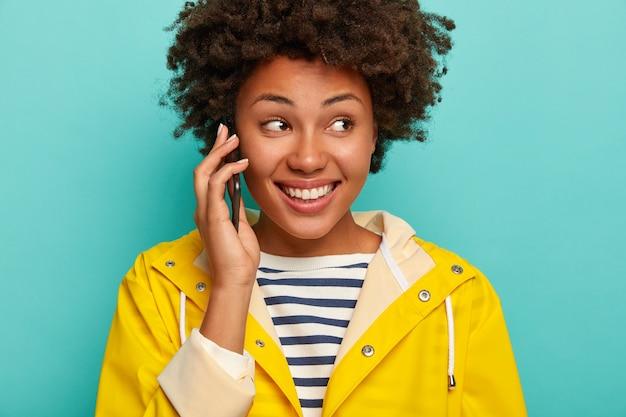 巻き毛の女性のクローズアップショットは幸せな表情をしており、陽気な話をするために親友を呼び出し、黄色の防水レインコートを着て、脇に集中し、青い背景に対して屋内に立っています。 無料写真