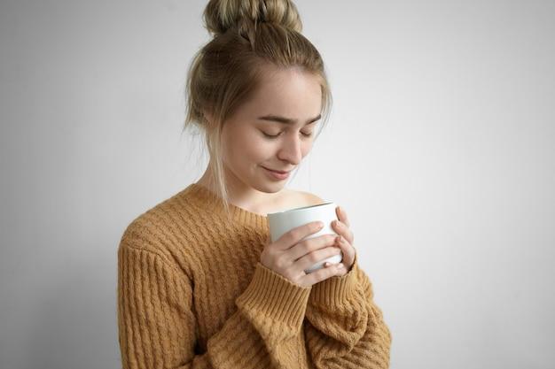 大きなカップから甘い暖かいココアを楽しんで、目を閉じて、温かい飲み物の良い香りを吸い込んでいる居心地の良いニットセーターのかわいいかわいい女の子のクローズアップショット。飲料、休息、レジャー、リラクゼーション 無料写真