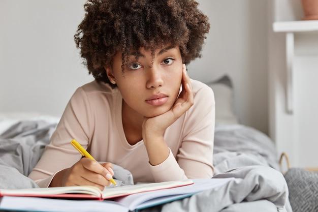 暗い肌の女の子のクローズアップショットは、ノートにアイデアのメモを作成し、ベッドに横たわっています 無料写真