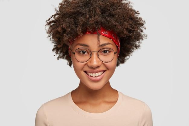 부드러운 표정, 즐거운 미소로 친절하고 쾌활한 아프리카 Amrican 여성의 총을 닫고 여름 휴가에 놀라운 여행을 기뻐하고 둥근 안경을 쓰고 흰색 모델을 착용합니다. 무료 사진