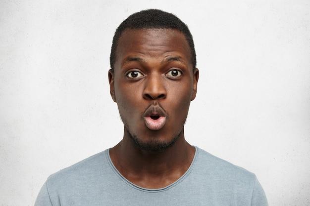 何気なく唇をふくれっ面と眉を上げる服を着て面白い若いアフリカ系アメリカ人のショットを閉じる 無料写真