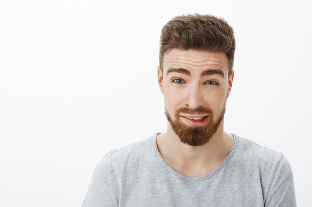 ひげと茶色の髪型の眉毛を上げている有罪のかわいいボーイフレンドのショットを閉じる 無料写真