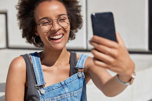 행복 한 아프리카 계 미국인 여자의 총을 닫습니다 앞에 셀룰러 보유, 광범위 하 게 미소, 셀카 초상화, 높은 정신에 걸리고, 유행 여름 옷을 입고 야외 휴식을 즐깁니다. 여가 무료 사진