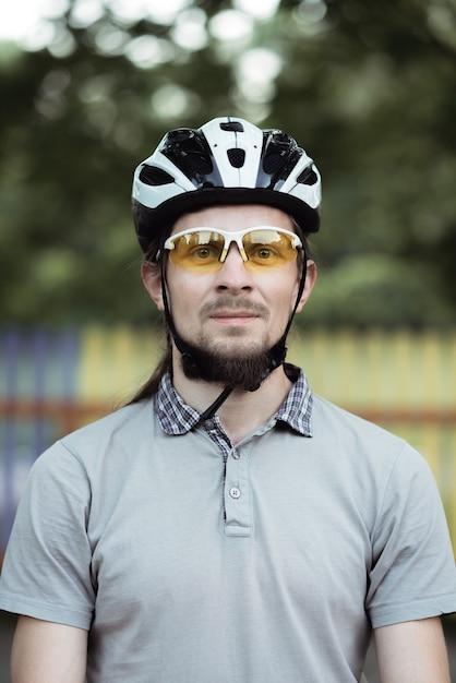 보호용 헬멧과 노란색 선글라스를 쓰고 수염을 가진 행복 한 매력적인 젊은 남자의 총을 닫습니다. 프리미엄 사진