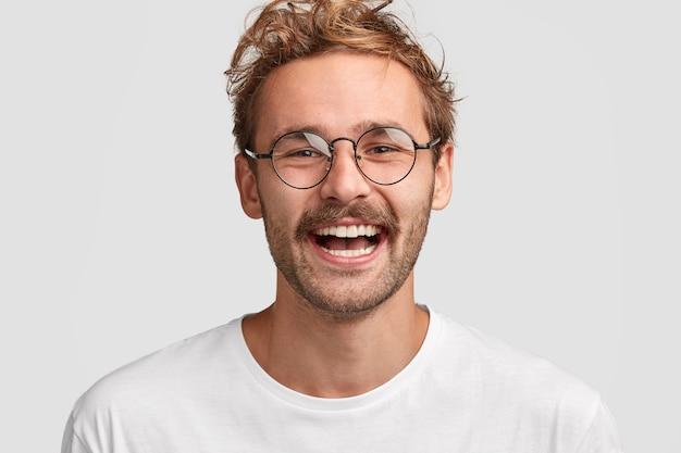 丸いメガネで幸せなスタイリッシュな男のショットをクローズアップ、顔に前向きな笑顔を持っている、給料を受け取ってうれしい、新しい購入にお金を使うつもり 無料写真