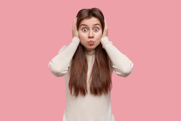 素敵な黒髪の若い女性のクローズアップショットはしかめっ面を作り、唇を吐き出し、両手で耳を覆い、何も聞こえません 無料写真
