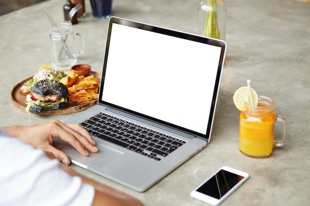 一般的なラップトップコンピューターのタッチパッドに人間の手のショットを閉じます。白人の学生が彼の卒業証書プロジェクトに取り組んでいるノートpcでキーボード操作 無料写真
