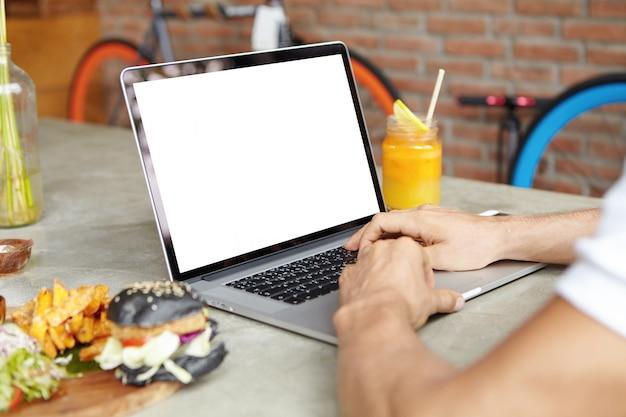 오픈 일반 노트북의 키보드에 사람의 손에 총을 닫습니다. 그의 노트북 컴퓨터에서 온라인으로 공부하는 남자 학생 무료 사진