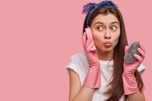 Крупным планом красивая горничная делает гримасу, носит повязку на голову, белую футболку и резиновые защитные перчатки, держит губку возле уха, веселится Бесплатные Фотографии