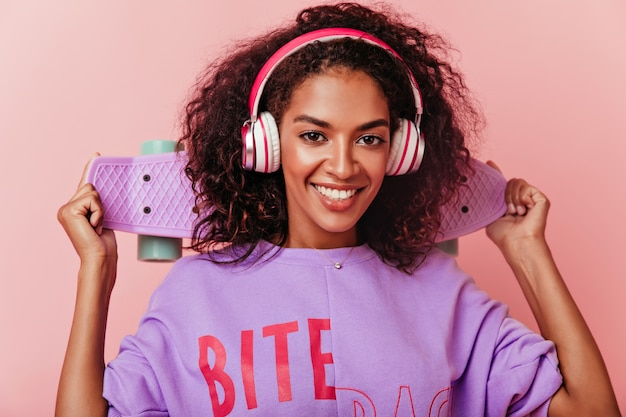 트렌디 한 큰 헤드폰에서 세련 된 흑인 여성의 클로즈업 샷. 스케이트 보드를 들고 음악을 듣고 놀라운 웃는 갈색 머리 소녀. 무료 사진