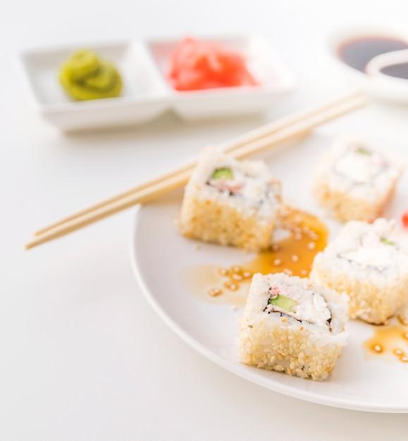 背景をぼかした写真の寿司プレートのショットを閉じる 無料写真