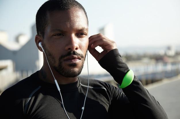 그의 귀에 헤드폰을 넣어 수염을 가진 젊은 흑인 남자의 근접 샷. 결정된 스포츠맨은 일출시 장거리 달리기와 운동을 할 준비가되었습니다. 스포츠 피트니스 추적기를 착용하는 선수. 무료 사진