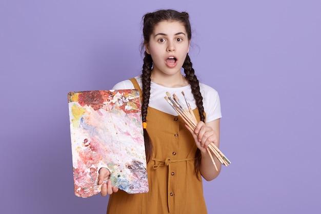 カラーパレットとペイントブラシを手で保持している若い女性アーティストのショットを閉じる 無料写真