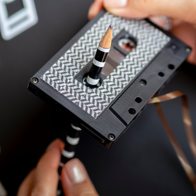 Close up shot person repairing cassette tape with pencil Free Photo